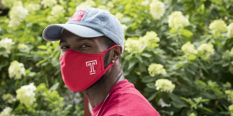 A Temple community member wearing a Temple-branded mask.