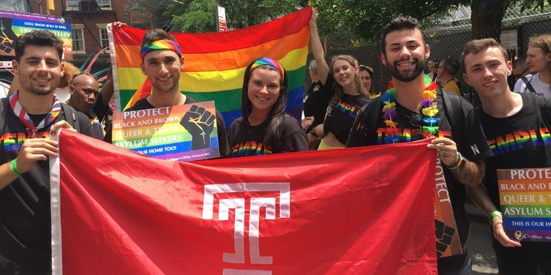 Students and alumni carrying a rainbow Pride flag and a Temple Flag.