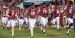 Temple football players running onto field for a game