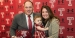 Geoff Collins holding a Temple helmet and smiling with wife and baby daughter.