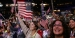 Attendees waving American flags in the crowd of the Democratic National Convention.
