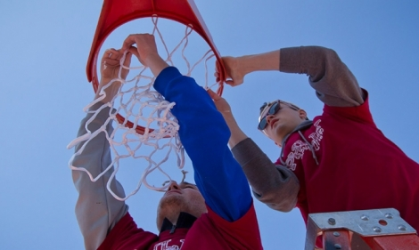Two male student volunteers hanging a basketball net at Amos Recreation Center.