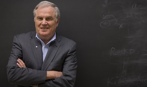 Thomas Edwards standing in front of a chalkboard with his arms crossed.