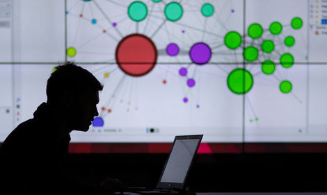 man on a laptop in silhouette with data visualization on screen