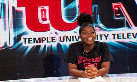 A teenage girl sitting at the anchor desk at TUTV