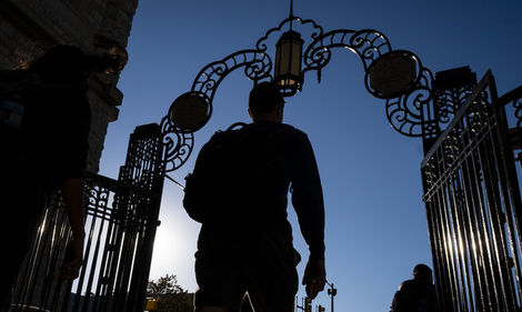 A student in silhouette walks through gates on Temple's Main Campus.