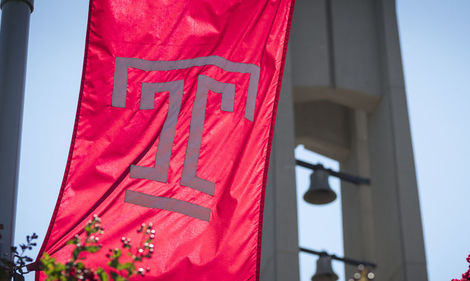 the Temple T flag waving in front of the bell tower on a clear, sunny day.