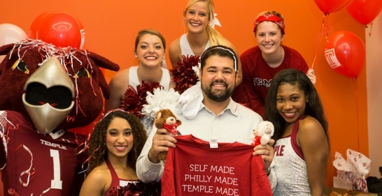 Temple cheerleaders and Hooter surprise an alumnus at the Comcast Building.