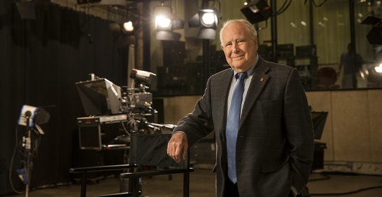 Lew Klein standing in a studio near a camera
