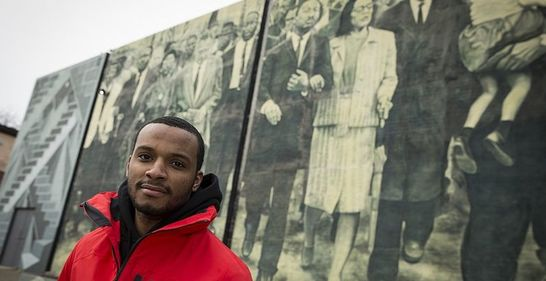 Hazim Hardeman standing in front of a mural near Main Campus.
