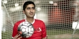 Haseeb Goheer holding a soccer ball in front of a goal net.