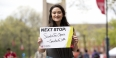 """Courtney Banks holding a sign that says """"Next stop: Santa Fe Opera."""""""