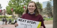 """Hope Watson holding a sign that says """"Next stop: University of Cambridge""""."""