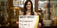 A woman holding a sign that reads next stop: my independent pharmacy.