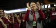 President Richard M. Englert clapping in the stands among Temple students at a basketball game.
