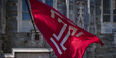 Image of the cherry and white Temple 'T' flag outside of Sullivan Hall on Main Campus.
