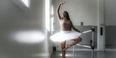 A Black woman in white tutu practicing ballet at a barre in a dance studio.