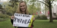 "Maggie Andresen holding a sign that says ""Next stop: Rwanda""."