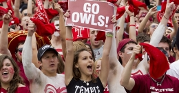 A group of students cheering at a Temple athletic event.