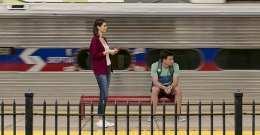 Two students waiting for a train at Temple University's SEPTA Regional Rail Station as a train passes by.