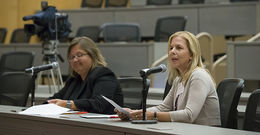 Two women sitting at a table and one is speaking into a microphone.