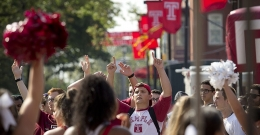 A group of students wearing Temple gear on campus.