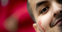 """A close up of a man with a red Temple """"T"""" painted on his face."""