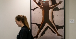 a student walking by artwork