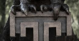 """a close up of Main Campus' Owl statue's talons gripping the Temple """"T"""""""