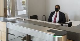 A security guard on campus wearing a mask and sitting behind a Plexiglas barrier at the entrance of a campus building.