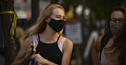 Students smiling and wearing masks on campus