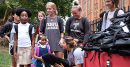 Temple student athletes distribute backpacks to local school students