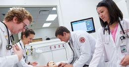 medical students practicing on a mannequin