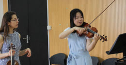 A Boyer professor instructing a student in violin