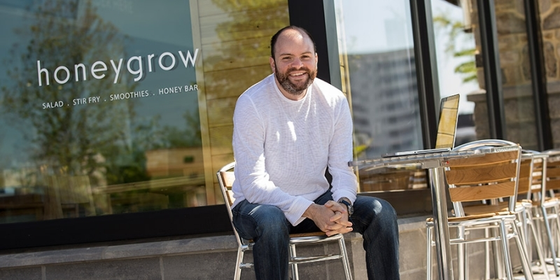 Justin Rosenberg sitting at a table outside of a honeygrow location.