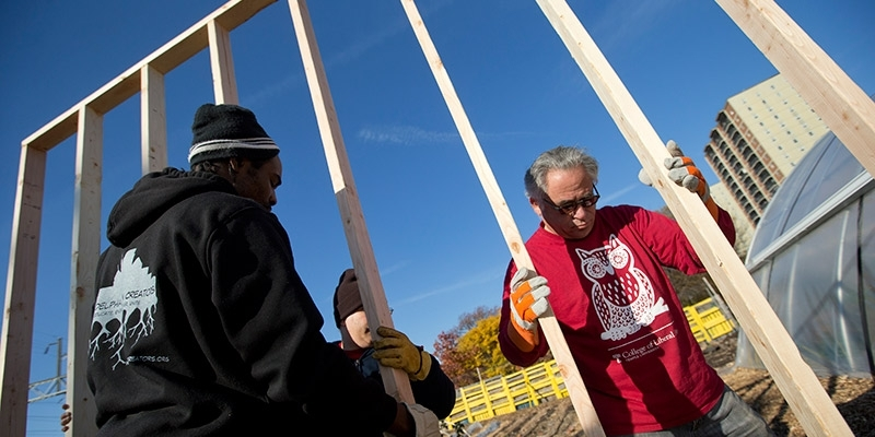 Temple volunteers framing a house on Global Day of Service.
