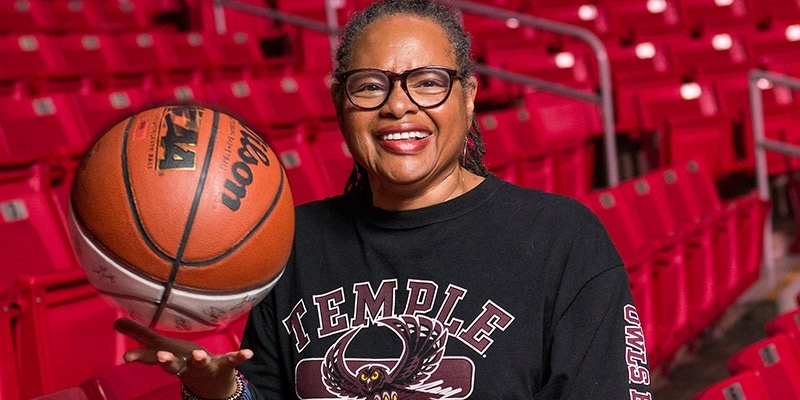 Professor Karen Turner poses with a basketball in the Liacouras Center.