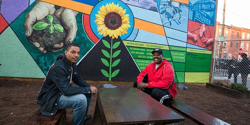 Two men sitting in front of a new colorful mural in North Philadelphia