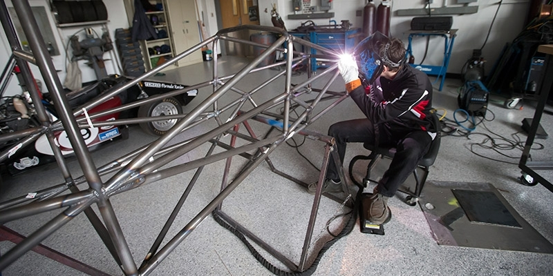 A Temple engineering students welds a portion of a race car.