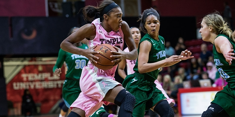 A Temple women's basketball player holding the ball while making a play.