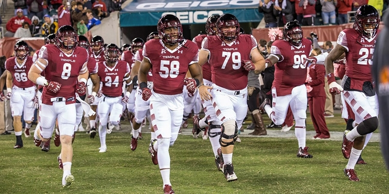 Temple football players running on to the field.