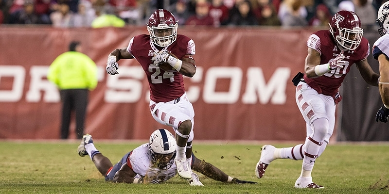 A Temple football player dodging a tackle in the game against UConn.