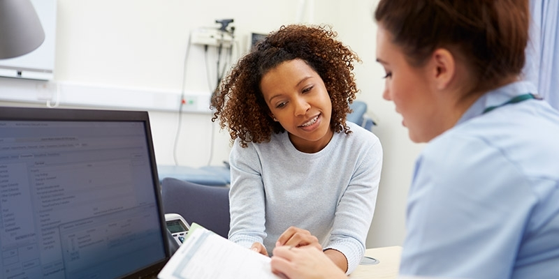A patient meeting with a clinician in an office.