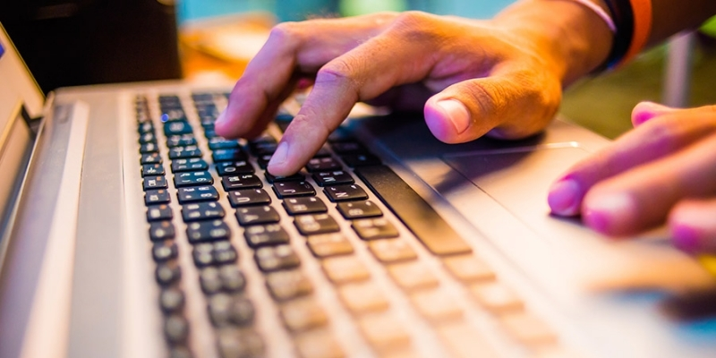 Hands resting on the keyboard of a laptop.