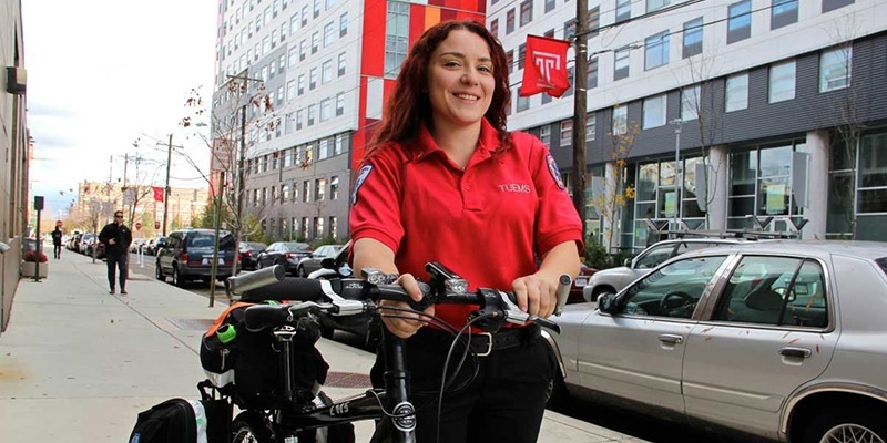 Danielle Thor on campus with the bicycle she uses as an EMT.