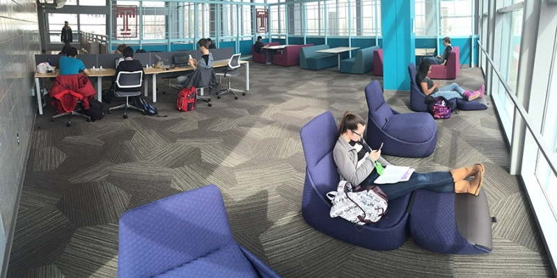 A female student sitting in a blue chair in the refurbished Owls' Nest.