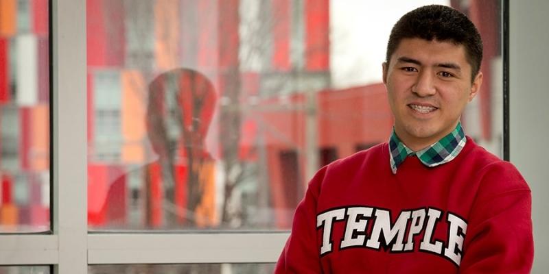 Matthew Velasquez standing in front of a window, wearing a cherry Temple sweatshirt.