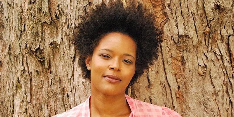 Yolanda Wisher posing in front of a tree.