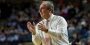 Coach Dunphy coaching from the sideline of a basketball court.
