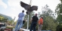 construction workers watch as a bronze owl statue is lowered